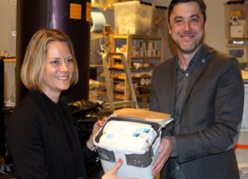 Maria Blomberg, på PostNord Frimärken, tar emot de 249 rymdbreven från projektledaren för PoGOLite professor Mark Pearce.