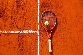 Tennisracket med boll på bana.